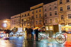 Horse-drawn μεταφορά πριν από το Sukiennice στο κύριο τετράγωνο αγοράς στην Κρακοβία, άποψη νύχτας, POL Στοκ φωτογραφία με δικαίωμα ελεύθερης χρήσης