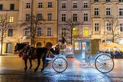 Horse-drawn μεταφορά πριν από το Sukiennice στο κύριο τετράγωνο αγοράς στην Κρακοβία, άποψη νύχτας, POL Στοκ εικόνες με δικαίωμα ελεύθερης χρήσης