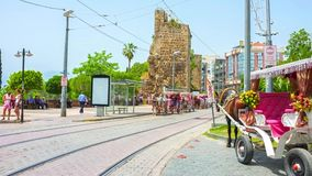 Horse-Drawn Carriage. ANTALYA, TURKEY - MAY 13, 2017: Time-lapse of Cumhuriyet Avenue with the tram lines, stations, horse carriages and ruins of the ancient stock footage