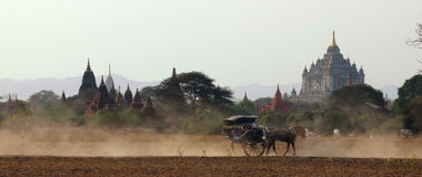 Horse-drawn carriage in Bagan. A horse-drawn carriage is driving along in front of the famous ancient That Byin Nyu Temple of Bagan. Bagan is a historic royal Royalty Free Stock Photo