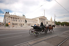 A horse-drawn carriage called fiaker passes by the Austrian Parliament building. Royalty Free Stock Image