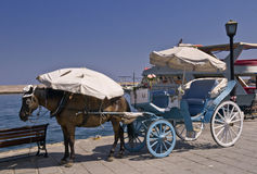 Horse-Drawn Carriage in Chania, Crete. A horse wearing a sunhat and blinkers is waiting for passengers near the waterfront. A canvas sunshade protects the horses Royalty Free Stock Images