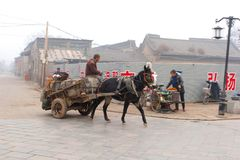 Traditional horse-drawn carriage in foggy walled town Pingyao, China Royalty Free Stock Photo