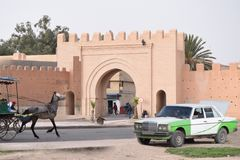 Horse drawn carriage in front of the city wall of Taroudant, Morocco. With an old taxi at the side stock photography