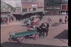 Horse drawn carriage riding through western town stock video