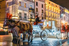 Horse-drawn carriage before the Sukiennice on The Main Market Square in Krakow. Night view, Poland Stock Photos