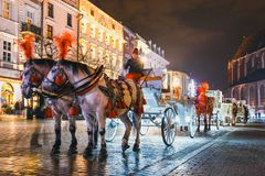 Horse-drawn carriage before the Sukiennice on The Main Market Square in Krakow, night view, Po. Krakow, Poland - December 15, 2017: Horse-drawn carriage before Royalty Free Stock Photography