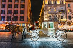 Horse-drawn carriage before the Sukiennice on The Main Market Square in Krakow, night view, Po. Krakow, Poland - December 15, 2017: Horse-drawn carriage before Stock Images