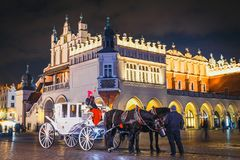 Horse-drawn carriage before the Sukiennice on The Main Market Square in Krakow, night view, Po. Krakow, Poland - December 15, 2017: Horse-drawn carriage before Stock Image