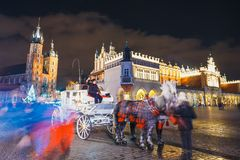 Horse-drawn carriage before the Sukiennice on The Main Market Square in Krakow, night view, Po. Krakow, Poland - December 15, 2017: Horse-drawn carriage before Royalty Free Stock Photos