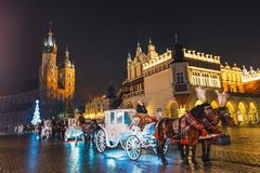 Horse-drawn Carriage before the Sukiennice on The Main Market Square in Krakow, night view, Pol. Krakow, Poland - January 22, 2017: Horse-drawn Carriage before Stock Images