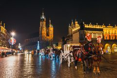 Horse-drawn carriage before the Sukiennice on The Main Market Square in Krakow, night view, Pol. Krakow, Poland - January 22, 2017: Horse-drawn carriage before Stock Image