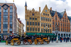 Horse-drawn carriage with tourists in Grote Markt, Brugge, Belgi Stock Image