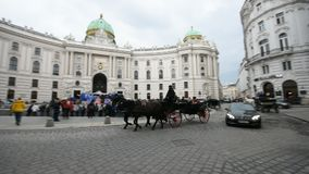 Horse-drawn carriage in Vienna. VIENNA, AUSTRIA - SEPTEMBER, 2017: A horse-drawn carriage called fiaker passing by the Hofburg palace at Michaelerplatz with stock video footage