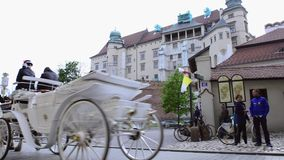 Horse drawn carriages with guides in front of Wawel castle in Krakow, Poland. Stock Photos