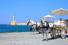 Horse drawn carriages and lighthouse, Chania. Royalty Free Stock Image
