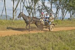 Horse drawn cart and three people traveling through countryside of central Cuba Royalty Free Stock Images