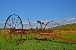 Horse Drawn Dump Rake. A refurbished horse drawn dump rake parked near a cornfield in the autumn colors Stock Photo