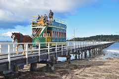 Horse drawn tram pulled by Clydesdale horse along the causeway from Granite Island to Victor Harbor. This image is taken at South Australia whereby the service stock image