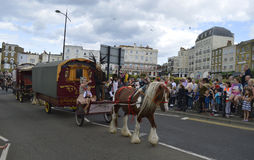 Horse drawn wagons and performers lead the Margate Carnival Parade. MARGATE,UK-August 6:Crowds watch members of the Sangar family take part in the annual Margate royalty free stock image