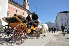 Horse driven carriage with tourists in Salzburg. SALZBURG – MARCH 13: Horse driven carriage with tourists in Mozart square, visiting the famous city of Stock Images