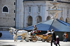Horse driven carriage with tourists in Salzburg Royalty Free Stock Photos