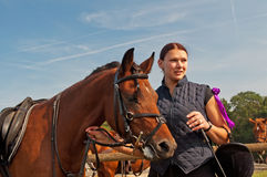 Horse and Equestrienne. Pretty girl and bay horse during the sunny day Royalty Free Stock Photography