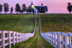 Horse Farm. White fences in front of a stable at a horse farm in Kentucky at sunset Stock Image