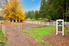 Horse farm with white fence and fall colorful leaves. Royalty Free Stock Photos