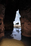 Horse galloping past cave