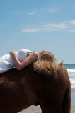 Horse and girl at beach. Girl relaxing on a chestnut pony at the beach in summertime Royalty Free Stock Photo