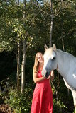 Horse Girl. Pretty girl in a red dress standing with her horse Stock Image