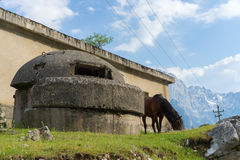Horse grassing near Bunker in front of Albanian mountains scenery. Taken during a 9 hour hike on the Valbona pass Stock Photos