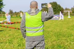 Horse handler take pictures on smart phone Royalty Free Stock Photo