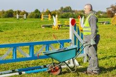 Horse handler with wheelbarrow on hurdle field Stock Photos