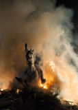 Horse with its rider rapidly breaking through the fire Stock Photo