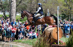 Horse jumping a log in a corss country event. Lexington, Kentucky - April 26, 2014: Hawley Bennett-Awad riding Gin & Juice at the 2014 Rolex Three-Day Event at Royalty Free Stock Photography