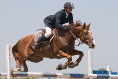 Horse jumping show. Chestnut stallion and the rider jumping on horse jumping show Stock Photo