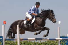 Horse jumping show. Black stallion and the rider jumping on horse jumping show Stock Photo
