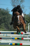 Horse jumping sport. A male caucasian horse rider jumping a hurdle with his beautiful brown sport horse at the riding school outdoors in a competition of an Royalty Free Stock Photography