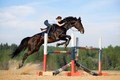 Horse jumping. Young girl jumping on bay horse - riding horseback Stock Photo