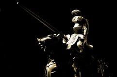 Horse knight. Toy statue of knight on horseback on black background Stock Photos