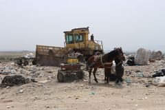Horse mounted on a scavenger cart and a broken waste compactor in a landfill site. A scavenger taking a break next to his horse mounted cart in a landfill stock images