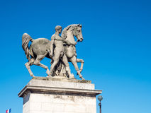 Horse and naked man sculpture in Paris. Beautiful horse and naked man sculpture near Eiffel tower in Paris, France, under blue sky Stock Images