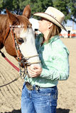 Horse and Owner. A barrel racing horse and rider in an outdoor arena. The rider is a female wearing a cowboy hat. The horse nuzzles her hand Royalty Free Stock Images