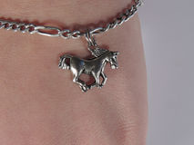 Horse pendant. Small bijou horse pendant on chain on the wrist of young girl Stock Photo