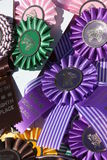 Horse prize rosettes. Closeup of colorful assortments of awards or prize rosettes with image of horses, equestrian event stock photo