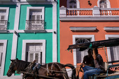 Horse pulling carriage in front of colorful colonial facade. Cienfuegos, Cuba on December 28, 2016: A brown horse is pulling a blue carriage in front of a Stock Photo