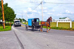 A horse pulling a cart across. A horse parking with a cart at a parking lot Stock Image