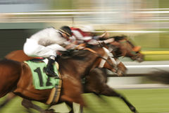 Horse Race. Abstract motion blur of three jockeys and thoroughbred horses racing toward the finish. Shot a slow shutter speed to enhance motion effect stock image